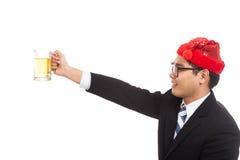 Азиатский бизнесмен с красными приветственными восклицаниями шляпы рождества с кружкой пчелы Стоковые Изображения RF