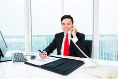 Азиатский бизнесмен телефонируя в офисе стоковые изображения