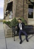 Азиатский бизнесмен усмехаясь и говоря на мобильном телефоне на стенде Стоковые Фото