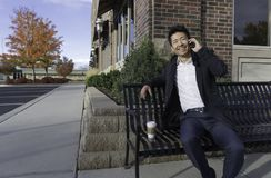 Азиатский бизнесмен усмехаясь и говоря на мобильном телефоне на стенде Стоковое Фото