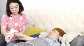 Азиатский больной мальчик, лежа в кровати, мать проверяя его температуру стоковое фото