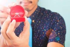 Азиатский бородатый человек держа коробку ` s кольца с бриллиантом, влюбленность и wedding c Стоковое Изображение