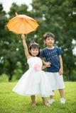 Азиатский брат и сестра имея потеху в парке Стоковая Фотография