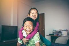 Азиатский брат с его сестрой на езде автожелезнодорожных перевозок и усмехаясь happ стоковая фотография