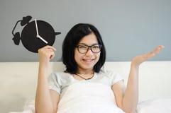 Азиатский будильник взятия женщины, и счастлив на ее кровати стоковые фотографии rf