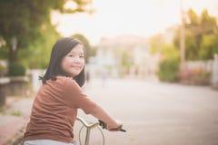Азиатский велосипед катания девушки в солнечном свете Стоковая Фотография