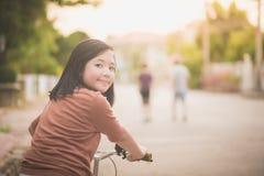 Азиатский велосипед катания девушки в солнечном свете Стоковые Изображения