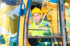 Азиатский водитель экскаватора лопаткоулавливателя на строительной площадке Стоковое Фото