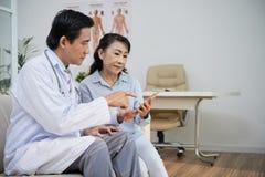 Азиатский врач советуя с старшим пациентом стоковые фото