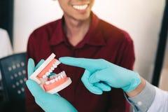 Азиатский дантист указывая к dentures и описывает pro стоковые изображения rf