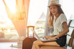 Азиатский девочка-подросток использует компьтер-книжку для того чтобы проверить электронную почту или социальную сеть стоковые фото