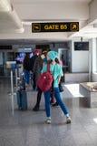 Азиатский девочка-подросток использует smartphone к проверочному полету на международном аэропорте для того чтобы путешествовать  стоковая фотография rf