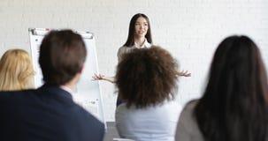 Азиатский диктор коммерсантки на представлении с группой в составе бизнесмены спрашивая вопросы во время встречи конференции видеоматериал