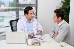 Азиатский доктор советует с молодым пациентом стоковое фото