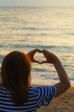 Азиатский девочка-подросток делая форму сердца в небе Стоковые Изображения