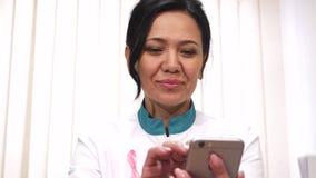 Азиатский женский доктор используя ее умный телефон на smilin работы жизнерадостно стоковая фотография rf