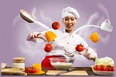 Азиатский женский шеф-повар в кухне колдует Стоковые Изображения