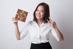 Азиатский знак победы выставки женщины с подарочной коробкой Стоковое фото RF