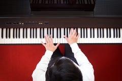 азиатский играть рояля человека Взгляд сверху с красной предпосылкой пола Стоковое Фото