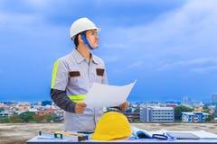 Азиатский инженер по строительству и монтажу держа светокопию на конструкции si Стоковые Фотографии RF