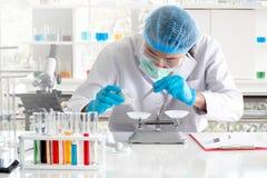Азиатский исследователь ученого или химика используя механический масштаб к собирая и измеряя образцу на лаборатории стоковые изображения rf