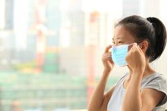Азиатский лицевой щиток гермошлема носки женщины в городе стоковое фото rf