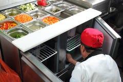 Азиатский кашевар в citchen работая на vegetable баре шведского стола Стоковые Фото