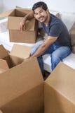 Азиатский китайский корейский человек распаковывая коробки двигая дом Стоковое Изображение RF