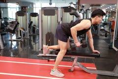 Азиатский китайский человек в молодом человеке ŒFitness ¼ ï спортзала в спортзале делая тренировки с гантелями Стоковые Фото