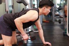 Азиатский китайский человек в молодом человеке ŒFitness ¼ ï спортзала в спортзале делая тренировки с гантелями Стоковая Фотография RF