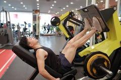 Азиатский китайский человек в тренировке человека спорта ŒFitness ¼ ï спортзала прочности ноги в спортзале Стоковые Изображения