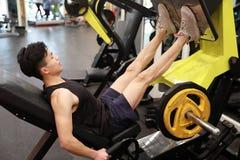 Азиатский китайский человек в тренировке человека спорта ŒFitness ¼ ï спортзала прочности ноги в спортзале Стоковое Изображение