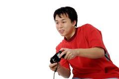 азиатский компьютер наслаждаясь игрой его детеныши Стоковое Изображение