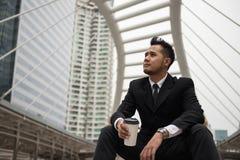 Азиатский кофе питья бизнесмена в городе стоковое изображение rf