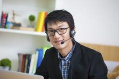 Азиатский красивый оператор человека на работе, связи c объявления дела стоковые фотографии rf