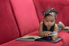 Азиатский малыш младенца лежа вниз на красной книге чтения софы Стоковая Фотография RF