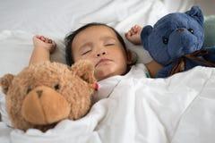 Азиатский малыш спать с плюшевым медвежонком на белых кровати, подушке и листе Стоковые Изображения