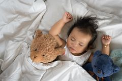 Азиатский малыш спать с плюшевым медвежонком на белых кровати, подушке и листе Стоковая Фотография RF