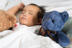 Азиатский малыш спать с плюшевым медвежонком на белых кровати, подушке и листе Стоковое Фото