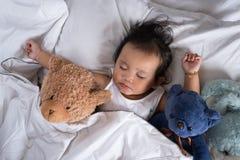 Азиатский малыш спать с плюшевым медвежонком на белых кровати, подушке и листе Стоковое фото RF