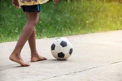 Азиатский мальчик играя старый футбол на улице, детях играет футбол стоковая фотография rf