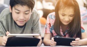 Азиатский мальчик и девушка играя игру на мобильном телефоне вместе со стороной улыбки стоковые изображения rf
