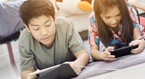 Азиатский мальчик и девушка играя игру на мобильном телефоне вместе со стороной улыбки стоковые фото