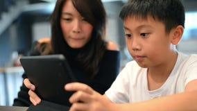 Азиатский мальчик и его мать используя цифровой планшет совместно акции видеоматериалы