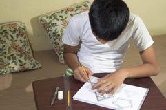 Азиатский мальчик уча и практикуя нарисовать формы 3D на тетради чертежа на коричневом столе дома Стоковая Фотография
