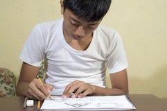 Азиатский мальчик уча и практикуя нарисовать формы 3D на тетради чертежа Стоковые Фото