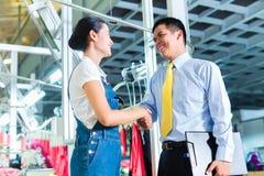 Азиатский мастер в фабрике ткани давая тренировку Стоковая Фотография RF