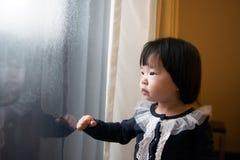 Азиатский малыш наблюдая снег Стоковые Изображения RF