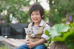 Азиатский мальчик держа американского котенка коротких волос Стоковое Изображение RF