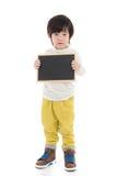 Азиатский мальчик держа черную доску на белой предпосылке изолированный Стоковые Изображения